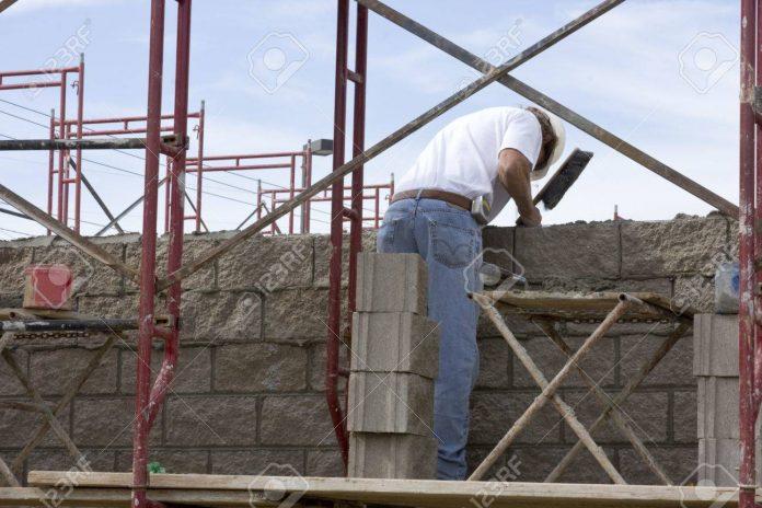 10909457 albanil de mason construir un muro con andamios - Un trabajador de la construcción en grave estado tras caer de un andamio